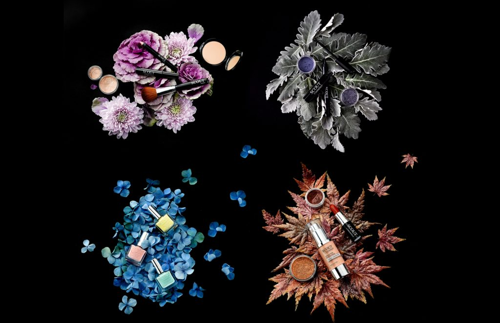 still life photography of scout cosmetics on leaves and flowers